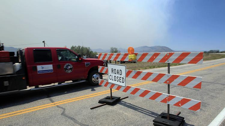 A fire truck passes by a roadblock to a wildfire as it continues to burn near Livermore, Colo., on Saturday, June 23, 2012. Authorities sent out 992 evacuation notices Friday due to the wildfire burning on more than 100 square miles in northern Colorado as winds pick up. (AP Photo/David Zalubowski)