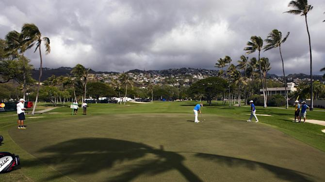 Carl Pettersson, center, of Sweden, putts on the 17th green during the first round of the Sony Open PGA Tour golf tournament, Thursday, Jan. 10, 2013, in Honolulu. (AP Photo/Marco Garcia)