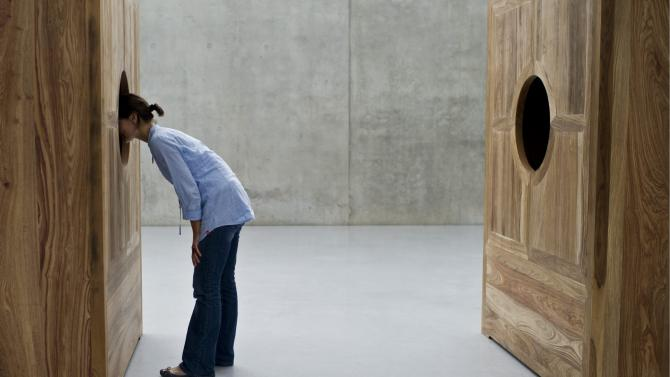"""A visitor looks at the installation """"Moon Chest"""" by Chinese artist Ai Weiwei, during the exhibition """"Art and Architecture"""" at the Kunsthaus Bregenz in Bregenz, Austria, Thursday, July 14, 2011. The Ai Weiwei """"Art and Architecture"""" exhibition lasts from July 16 to October 16, 2011. (AP Photo/Keystone/Ennio Leanza) GERMANY OUT AUSTRIA OUT"""
