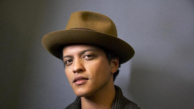 """American singer-songwriter and record producer Bruno Mars, born Peter Gene Hernandez, poses for a portrait on Monday, Nov. 5, 2012 in New York. Mars' recent appearance on """"Saturday Night Live"""" was more like Saturday Night Fever: He says he had so much fun hosting the show that he'd be happy to do it again. """"Whatever 'SNL' wants from me, they can always call me,"""" the smiling 27-year-old said in an interview Wednesday afternoon. """"I don't know who told them I can act or anything 'cause I can't. I don't know what they saw. (But) whatever they need from me, they can get.""""  (Photo by Dan Hallman/Invision/AP)"""