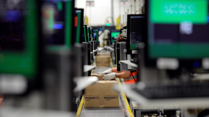 In this Thursday, Dec. 13, 2012 photo, amazon shipments are packaged in Koblenz, Germany. Amazon's fourth-quarter net income fell 45 percent, as sharply higher revenue failed to keep pace with increased spending on order fulfillment and digital content, a trend that's become the norm for the world's largest online retailer. (AP Photo/dapd, Harald Tittel)