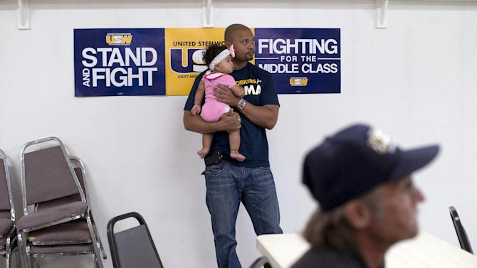 Ryan Roques holds his 8-month-old daughter, Peyton, while watching the presidential debate at the United Steelworkers Local 4856 Union Hall, Wednesday, Oct. 3, 2012, in Henderson, Nev. President Barack Obama and Republican presidential candidate Mitt Romney faced off, Wednesday night.  (AP Photo/Julie Jacobson)