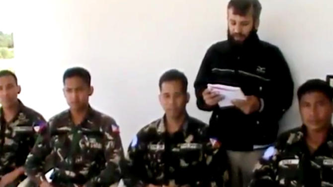 In this image taken from video obtained from the Ugarit News, which has been authenticated based on its contents and other AP reporting, a man reads a statement as four abducted Filipino UN peacekeepers are seen in Daraa, Syria, on Thursday, May 9, 2013. Tensions remained high on the Israeli-Syrian border on Thursday morning, two days after a Syrian rebel group abducted four UN peacekeepers. The abduction was the second such incident in the area in two months. The UN said the Filipino peacekeepers were detained on Tuesday while on patrol on the Golan Heights, a volatile Israeli-occupied area that separates Syria and Israel. (AP Photo/Ugarit News via AP video)