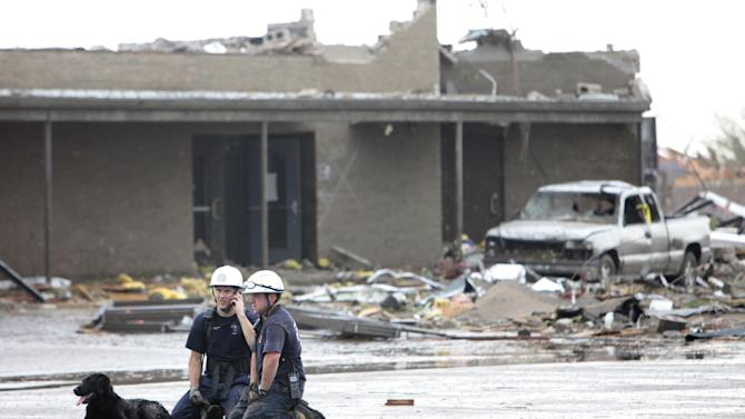 Searchers rest outside the Briarwood Elementary School after the tornado destroyed the school , Monday,  May 20, 2013. (AP Photo/ The Oklahoman,  David McDaniel)