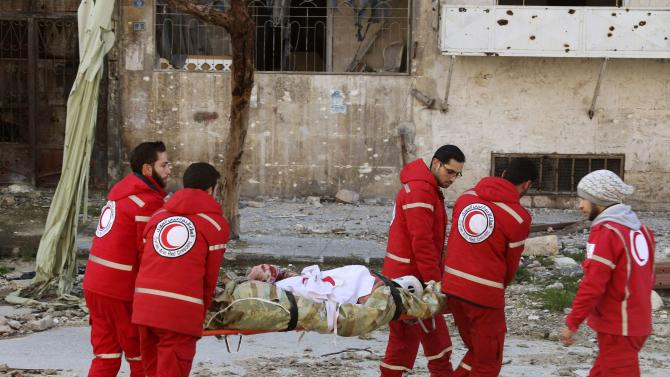 Members of the Syrian Arab Red Crescent transport a sick civilian on a stretcher in the rebel-controlled area of Aleppo's Bustan al-Qasr, as they head towards the government-controlled area of Aleppo to seek treatment