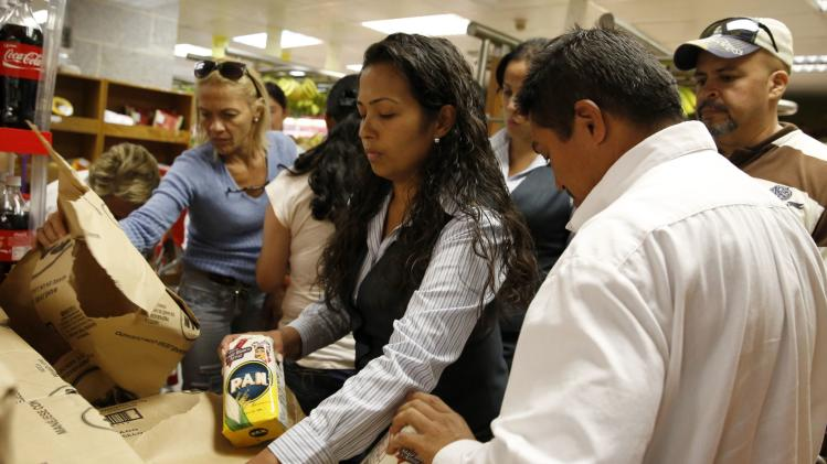 People grab packages of corn flour at a supermarket in Caracas