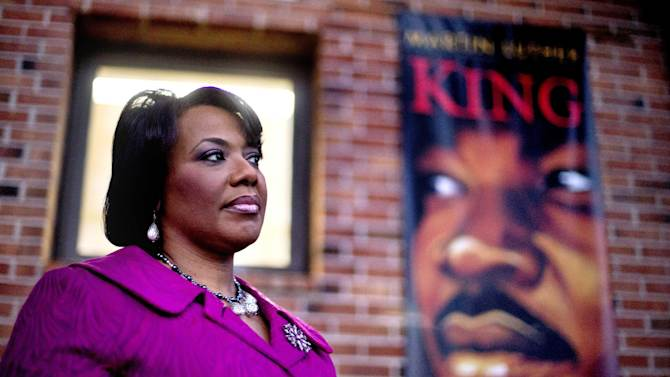 """In this Tuesday, Jan. 8, 2013 photo, Bernice King stands in the King Center next to a banner hanging in memory of her father, Dr. Martin Luther King Jr., in Atlanta. One of her father's quotes has been cited as one of America's essential ideals, its language suggestive of a constitutional amendment on equality: """"I have a dream that my four little children will one day live in a nation where they will not be judged by the color of their skin but by the content of their character."""" Yet today, 50 years after the Rev. Martin Luther King Jr.'s monumental statement, there is considerable disagreement over what this quote means when it comes to affirmative action and other measures aimed at helping the disadvantaged. (AP Photo/David Goldman)"""