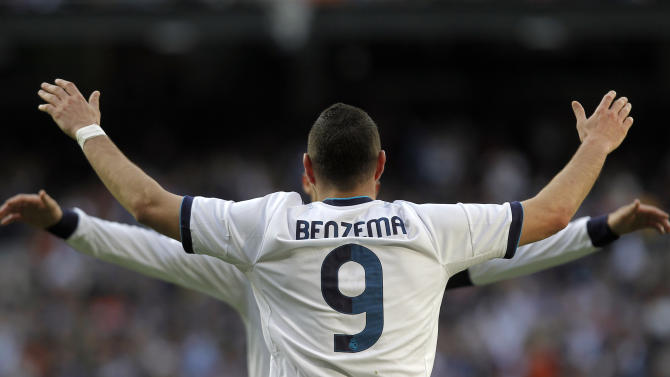 Real Madrid's Karim Benzema from France celebrates his goal with Cristiano Ronaldo from Portugal, partly seen, during a Spanish La Liga soccer match against Betis at the Santiago Bernabeu stadium in Madrid, Spain, Saturday, April 20, 2013. (AP Photo/Andres Kudacki)