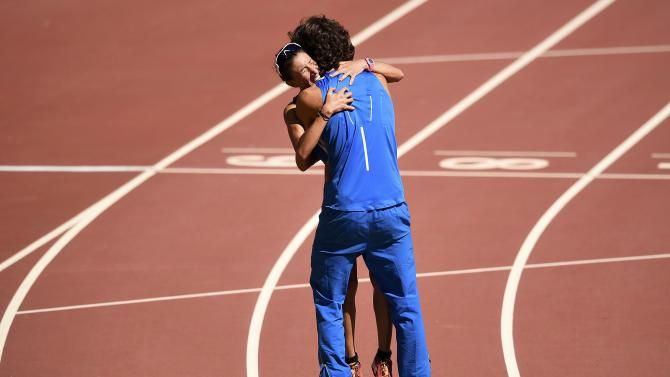 Antonella Palmisano of Italy (L) is hugged by Italian decathlete Gianmarco Tamberi after finishing the women's 20 km race walk final during the 15th IAAF World Championships at the National Stadium in Beijing