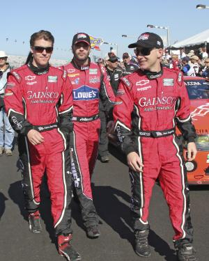 The Gainsco Chevrolet Riley drivers, from left, Alex Gurney, Jimmie Johnson, and Jon Fogarty, walk down pit road prior to the start of the Grand Am Rolex 24 hour auto race at Daytona International Speedway in Daytona Beach, Fla., Saturday, Jan. 29, 2011.(AP Photo/David Graham)