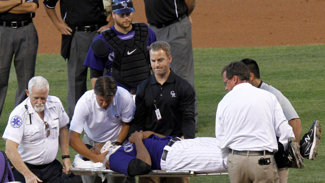 Colorado Rockies starting pitcher Juan Nicasio (44) is taken off the field by medical personnel after Washington Nationals' Ian Desmond hit him in the head with a line drive during the second inning of a baseball game Friday, Aug. 5, 2011, in Denver. (AP Photo/Barry Gutierrez)