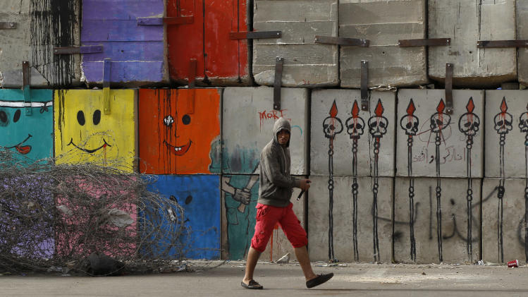 A man walks past graffiti painted on a wall near the Presidential Palace in Cairo, Egypt, Monday, Dec. 10, 2012. The Egyptian military on Monday assumed joint responsibility with the police for security and protecting state institutions until the results of a Dec. 15 constitutional referendum are announced. (AP Photo/Petr David Josek)
