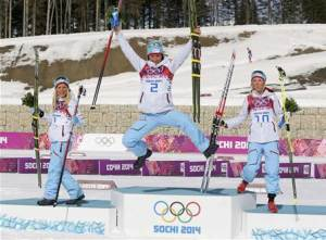Winner Norway's Bjoergen celebrates next to her compatriots, second placed Johaug and third placed Steira during a flower ceremony for the women's cross-country 30 km mass start free event at the Sochi 2014 Winter Olympic Games in Rosa Khutor