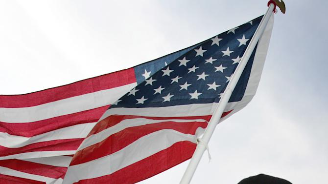 """FILE - In this July 24, 2005 file photo, Lance Armstrong, of Austin, Texas, carries the United States flag during a victory parade on the Champs Elysees avenue in Paris, after winning his seventh straight Tour de France cycling race. In 2012, Armstrong decided to give up the battle against doping charges, saying """"enough is enough"""" but acknowledging no wrongdoing. The move began his swift fall from being perhaps the nation's best-known cancer-fighting hero, and though he maintains he was victimized by a """"witch hunt"""" he was still stripped of all seven of his Tour de France victories. (AP Photo/Peter Dejong, File)"""