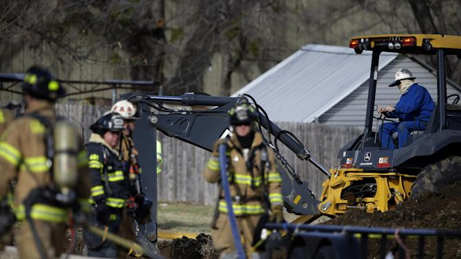 Lewisville fire fighters stand by with equipment and water hoses as a worker uses a back hole tractor to dig a hole about 100 feet away from a structure that exploded earlier Friday, Jan. 11, 2013, in Lewisville, Texas. An explosion Friday in a North Texas neighborhood leveled a home that is part of a local nonprofit's affordable housing program, injuring at least three men and scattering debris.(AP Photo/Tony Gutierrez)
