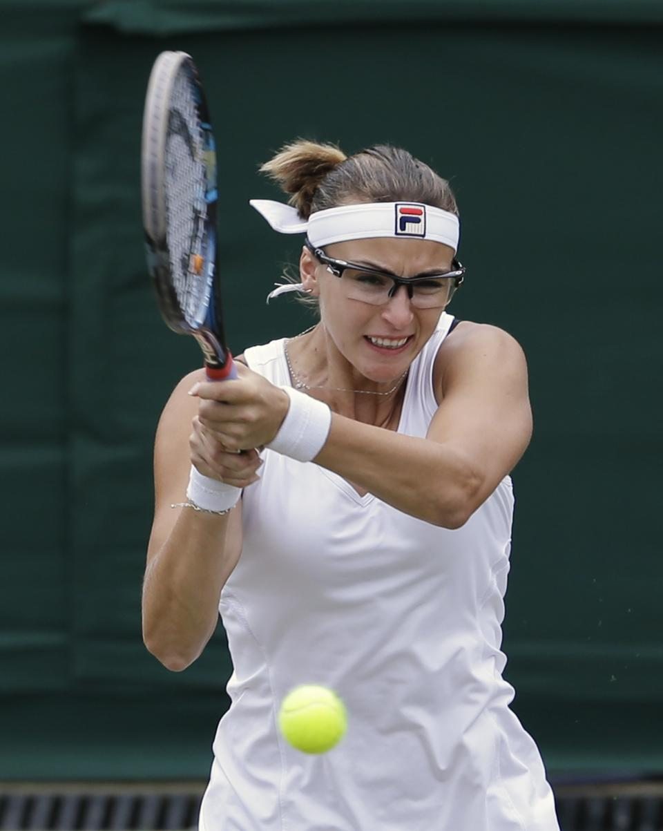 Yaroslava Shvedova of Kazakhstan returns a shot to Serena Williams of the United States during a fourth round women's singles match at the All England Lawn Tennis Championships at Wimbledon, England, Monday, July 2, 2012. (AP Photo/Kirsty Wigglesworth)