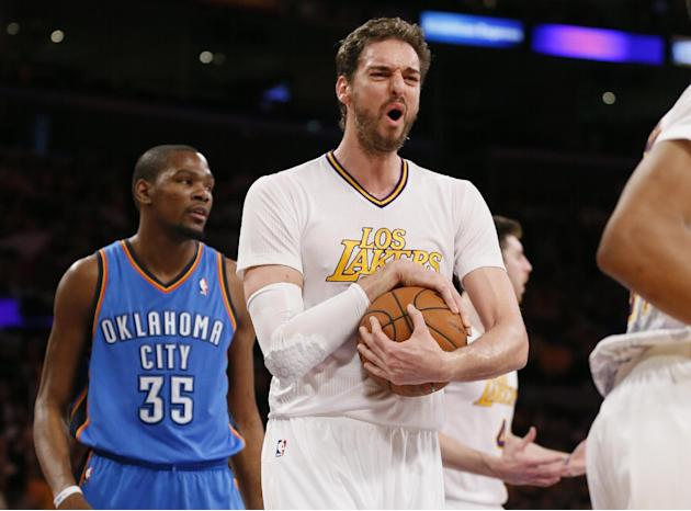 Los Angeles Lakers center Pau Gasol, center, reacts after a foul was called against teammate Ryan Kelley, rear right, as Oklahoma City Thunder small forward Kevin Durant, left, looks on during the fir
