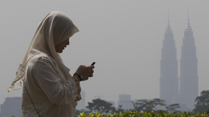 A woman checks her mobile phone as she walks past Malaysia's landmark Petronas Twin Towers in Kuala Lumpur, Malaysia, Thursday, June 20, 2013. Smoke haze is a nearly annual problem for Singapore and its northern neighbor Malaysia, often beginning in midyear when farmers in Indonesia seek to clear land cheaply by starting fires. It sometimes causes diplomatic strains as Malaysia and Singapore urge Indonesia to do more to prevent illegal burning. (AP Photo/Mark Baker)