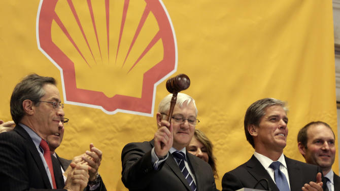 FILE - In this Friday, Feb. 1, 2013, file photo, Royal Dutch Shell CEO Peter Voser, center, gavels trading closed after ringing the closing bell of the New York Stock Exchange. Royal Dutch Shell reports quarterly earnings on Thursday, Oct. 31, 2013. (AP Photo/Richard Drew)