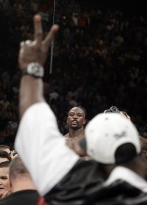 A member of his corner flashes a victory sign as Floyd…