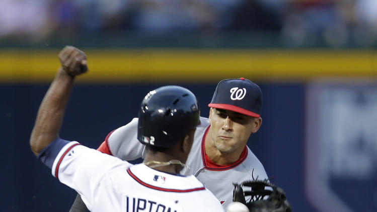 Washington Nationals shortstop Ian Desmond (20) handles the throw before tagging out Atlanta Braves' B.J. Upton (2) on a steal attempt in the third inning of a baseball game Tuesday, April 30, 2013, in Atlanta. (AP Photo/John Bazemore)
