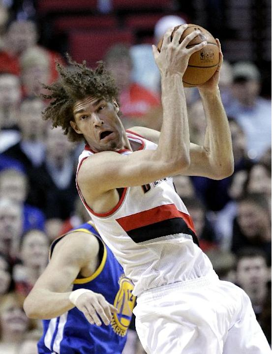 Portland Trail Blazers center Robin Lopez,  pulls in an offensive rebound against Golden State Warriors center Andrew Bogout, from Australia, during the first half of an NBA basketball game in Portlan