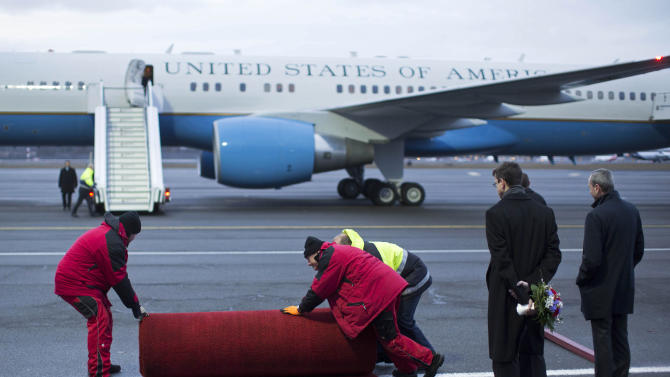 Airport staff pull the red carpet to the correct position in front of Air Force Two with U.S. Vice President Joe Biden and his wife Jill Biden onboard as U.S. Ambassador to Germany Philip D. Murphy, right, waits at the Tegel airport in Berlin, Germany, Friday, Feb. 1, 2013. Biden is expected to meet with Chancellor Angela Merkel in Berlin and to attend the annual Munich Security Conference in Munich that starts later Friday. (AP Photo/Gero Breloer)