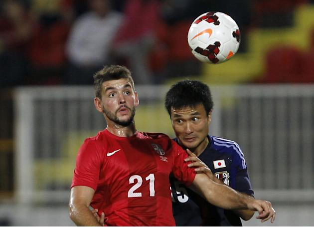 Serbia's Filip Djordjevic, left challenges for the ball with Japan's Yasuyuki Konno during their international friendly game, at Karadjordje stadium in Novi Sad, Serbia, Friday, Oct. 11, 2013