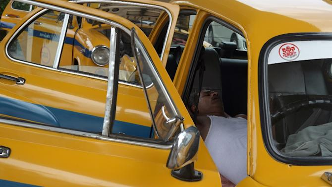 An Indian taxi driver rests in his parked car in Kolkata on May 25, 2015