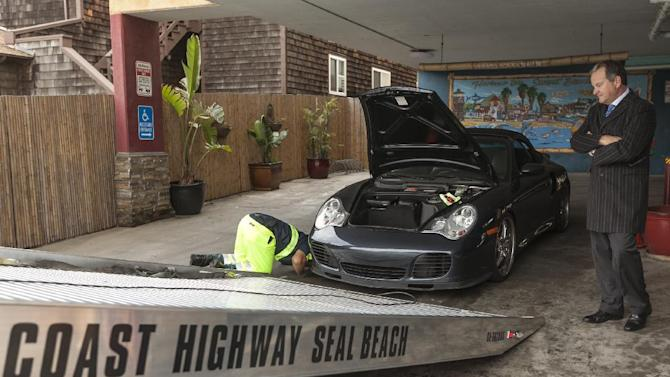 PowerTurbine president Fred Grether has his Porsche Sports car towed away after flood waters damaged its electric systems near the overflowed streets onto Pacific Coast Highway in the Sunset Beach area of Huntington Beach, Calif., Thursday, Dec. 13, 2012. Astronomical high tides have caused minor street flooding in some low-lying areas along the Southern California coast. (AP Photo/Damian Dovarganes)