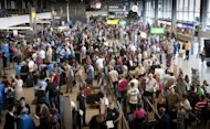 <p>This file photo shows travellers waiting in line to check in at Schiphol Airport in Amsterdam, in 2009. The European Commission plans to sanction EU members to nudge them into action on efforts to create a pan-European airspace that would cut costs and delays, according to an EU source.</p>