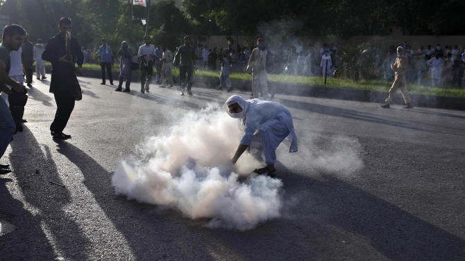 A Pakistani protester reaches for a tear gas canister fired by police, during clashes erupted as protestors tried to approach the U.S. embassy, in Islamabad, Pakistan, Thursday, Sept. 20, 2012. Hundreds of Pakistanis angry at an anti-Islam film that denigrates the religion's prophet clashed with police in the Pakistani capital Thursday, the most violent show of anger in a day that saw smaller demonstrations in Indonesia, Iran and Afghanistan. (AP Photo/Muhammed Muheisen)
