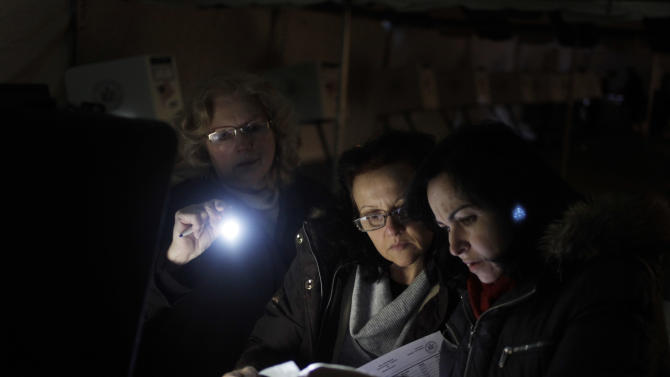 Poll workers Eva Prenga, right, Roxanne Blancero, center, and Carole Sevchuk try to start an optical scanner voting machine in the cold and dark at a polling station in a tent in the Midland Beach section of Staten Island, New York, Tuesday, Nov. 6, 2012. The original polling site, a school, was damaged by Superstorm Sandy. (AP Photo/Seth Wenig)