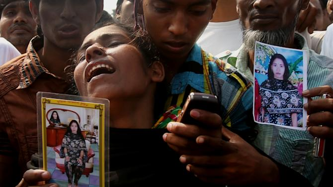 A woman mourns as she arrived in hopes to find her sister, seen in the photograph she is holding, among unclaimed bodies brought to a cemetery from the garment factory building collapse in preparation for a mass burial on Wednesday May 1, 2013 in Dhaka, Bangladesh. Several hundred people attended a mass funeral in a Dhaka suburb for 18 unidentified workers who died in the building collapse last week last week in the country's worst industrial disaster, killing at least 402 people and injuring 2,500. The bodies, rotting in the spring heat, were brought to the graveyard on the back of a flatbed truck.(AP Photo/Wong Maye-E)