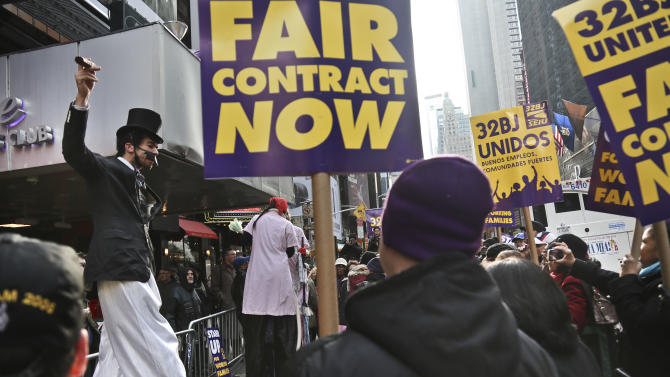 Stilt actors perform a skit during a protest of theater workers from union SEIU Local 32BJ, outside the Broadway League's office, before a vote authorizing a strike on Wednesday, Dec. 12, 2012, in New York. The union representing hundreds of Broadway theater cleaners, porters, elevator operators and bathroom attendants voted Wednesday to authorize its leaders to call a strike if a new contract isn't approved by the end of the month, (AP Photo/Bebeto Matthews)