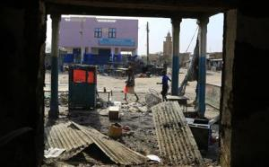 People walk past a burnt-out shop in Malakal