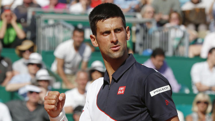 Novak Djokovic of Serbia reacts after scoring a point against Pablo Carreno Busta of Spain during their third round match of the Monte Carlo Tennis Masters tournament in Monaco, Thursday, April 17, 2014. Djokovic won 6-0, 6-1. (AP Photo/Michel Euler)