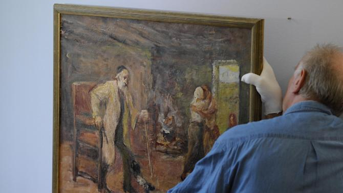 """In this picture taken Wednesday Sept. 7, 2011 an employee adjusts  the painting  """"Die Heimkehr des Tobias""""  ( The Return of Tobias)  by German-Jewish painter Max Liebermann (1847-1935)  at the Centrum Judaicum in Berlin. Israel's national museum has returned an impressionistic painting to the estate of its creator, the German-Jewish Max Liebermann.   The work was looted from the Jewish Museum in Berlin, where it was on loan from the artist, in the 1930. Following the end of World War II, the American-based Jewish Restitution Successor Organization (JRSO) collected orphaned art and distributed the pieces to Jewish institutions worldwide. Liebermann's painting was one of more than 1,000 works the JRSO delivered in 1955 to the Bezalel National Museum, the precursor to the Israel Museum.  (AP Photo/dapd/ Michael Gottschalk)"""