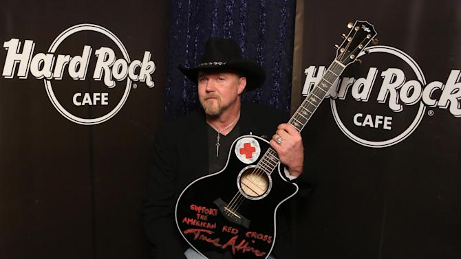 "IMAGE DISTRIBUTED FOR HARD ROCK INTERNATIONAL - Country star Trace Adkins donates the guitar he designed on NBC Network's ""All-Star Celebrity Apprentice,"" to Hard Rock to become a permanent part of the brand's world-famous memorabilia collection, on Wednesday, Feb. 27, 2013, in Hollywood, Calif. In exchange for the donation, Hard Rock International made a generous donation to The American Red Cross on Adkin's behalf during the show. (Photo by Rene Macura/Invision for Hard Rock International/AP Images)"