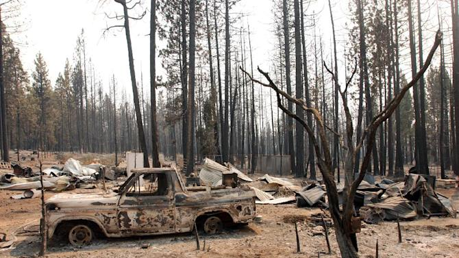 A damaged truck sits among other remains, Wednesday, Aug. 22, 2012, at a rural house site outside Manton, Calif., where a huge wildfire burned through on Saturday, forcing residents to evacuate. The Ponderosa Fire, which has scorched about 38 square miles, was 50 percent contained Wednesday morning, according to the California Department of Forestry and Fire Protection. The threat to homes about 35 miles east of Redding has dropped from 3,500 earlier this week to roughly 200 residences. (AP Photo/Jeff Barnard)