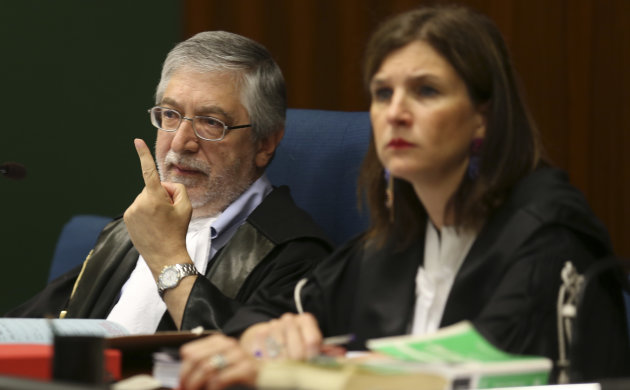 Judge Toni Adet Novik, left, gestures at the opening of a corruption trial against Finmeccanica, at the Busto Arsizio court, northern Italy, Wednesday, June 19, 2013. Trial opened Wednesday against th