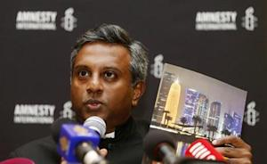 Amnesty International Secretary General Salil Shetty holds up a report during a news conference in Doha