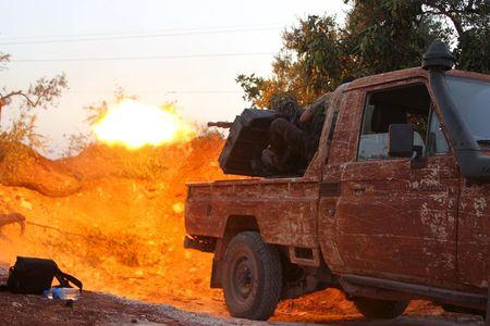 Members of al Qaeda's Nusra Front fire their weapon during an offensive to take control of the northwestern city of Ariha from forces loyal to Syria's President Bashar al-Assad, in Idlib province