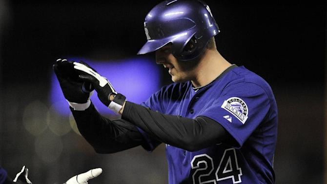 Colorado Rockies Jordan Lyles celebrates after hitting a single in the fifth inning of a baseball game against the Chicago White Sox on Monday, April 7, 2014, in Denver. The Rockies won 8-1