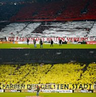 "File combination images of (lower) Borussia Dortmund fans behind a banner with the slogan ""the colours of the coolest town"" and (upper) Bayern Munich fans behind a banner reading ""the colours of the best club"", before the German soccer cup, DFB Pokal, quarter final match in Munich February 27, 2013. Champions League finalists Bayern Munich and Borussia Dortmund are the envy of soccer fans across Europe for the way the German clubs run their business as well as their success on the field. Bayern and Dortmund are the top two teams in the Bundesliga where clubs boast the largest crowds in Europe, keep ticket prices low, are largely profitable and have produced a crop of talented young players. TO GO WITH STORY SOCCER-CHAMPIONS/FINANCES REUTERS/Michael Dalder/Files  (GERMANY - Tags: SPORT SOCCER)"