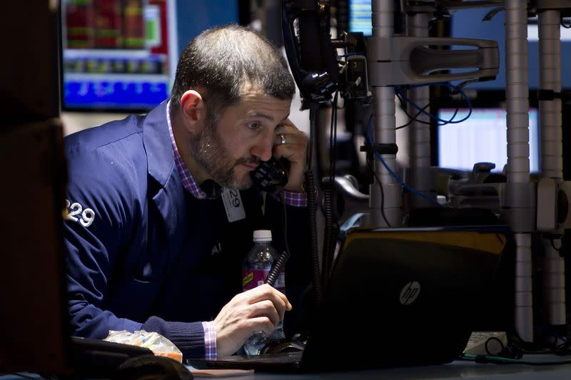 Wall Street falls 1 percent on earnings; Apple rallies late