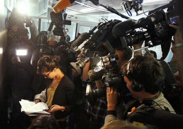 Lawyer Maud Sobel, left, is surrounded by reporters as she reads a statement by a French court which ordered a magazine publisher to hand over all digital copies of topless photos of Britain's Duchess of Cambridge and blocked the further publication of the images, at a court house in Nanterre, west of Paris, Tuesday Sept. 18, 2012. Under the ruling Tuesday, the French gossip magazine Closer faces a daily fine of euro 10,000 ($13,100) if it fails to hand over the photos taken during the royals' vacation in southern France and cannot disseminate them any further, including on its website and tablet app. (AP Photo/Remy de la Mauviniere)