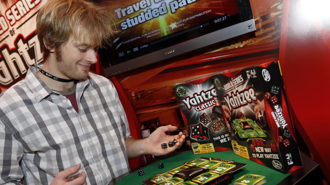 A demonstrator plays WORLD SERIES OF YAHTZEE in Hasbro's showroom at the American International Toy Fair, Saturday, Feb. 9, 2013, in New York. (Photo by Jason DeCrow/Invision for Hasbro/AP Images)