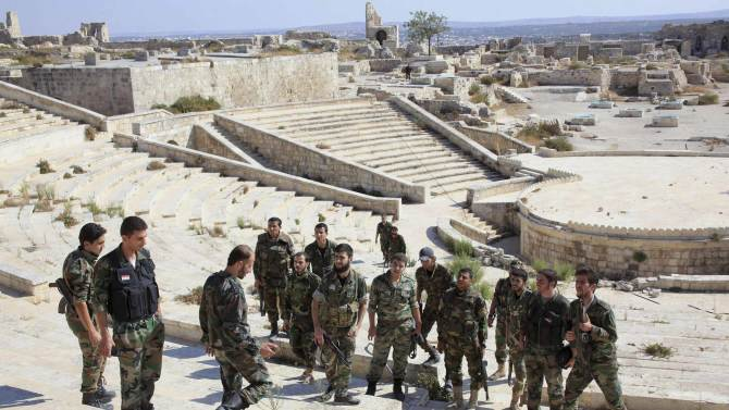 Forces loyal to Syria's President Bashar al-Assad hold their weapons as they gather in Aleppo's historic citadel
