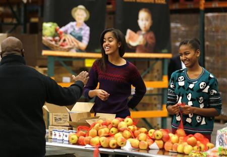 Malia and Sasha, daughters of U.S. President Obama hand out Thanksgiving food at the Capital Area Food Bank in Washington